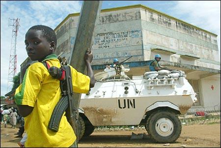 Boy with AK-47 Watches a UN Vehicle
